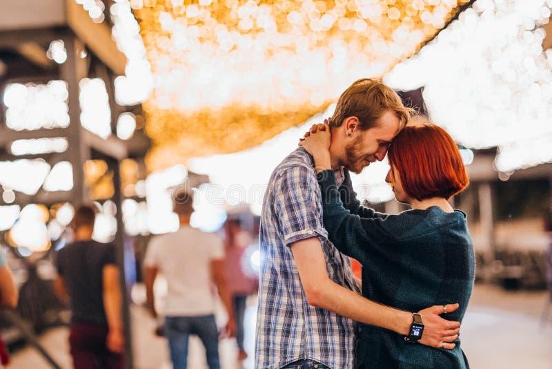Gelukkig paar die in de avond op lichte slingers omhelzen royalty-vrije stock fotografie