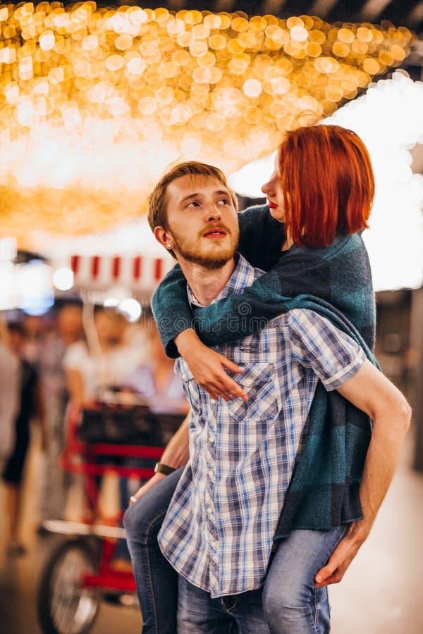 Gelukkig paar die in de avond op lichte slingers omhelzen stock afbeeldingen