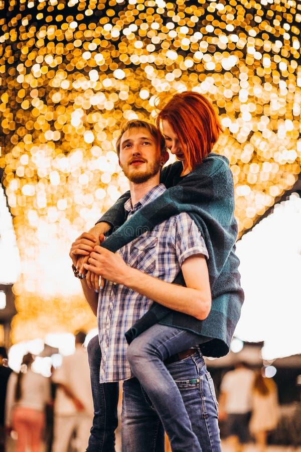Gelukkig paar die in de avond op lichte slingers omhelzen stock foto's
