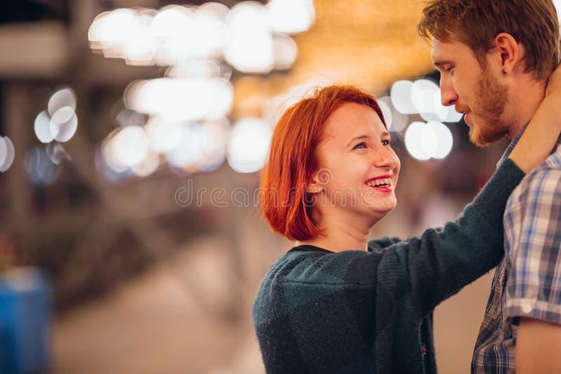 Gelukkig paar die in de avond op lichte slingers omhelzen royalty-vrije stock afbeeldingen