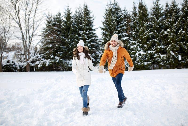 Gelukkig paar die in de wintersneeuw lopen stock foto's