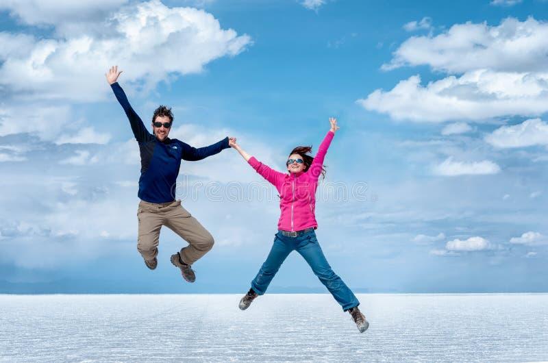 Gelukkig paar die in de Zoute Vlakten van Uyuni, Bolivië, Zuiden Americ springen royalty-vrije stock fotografie
