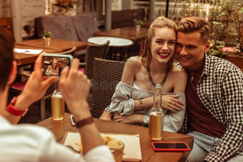 Gelukkig paar die door hun vriend bij de bar worden gefotografeerd stock foto