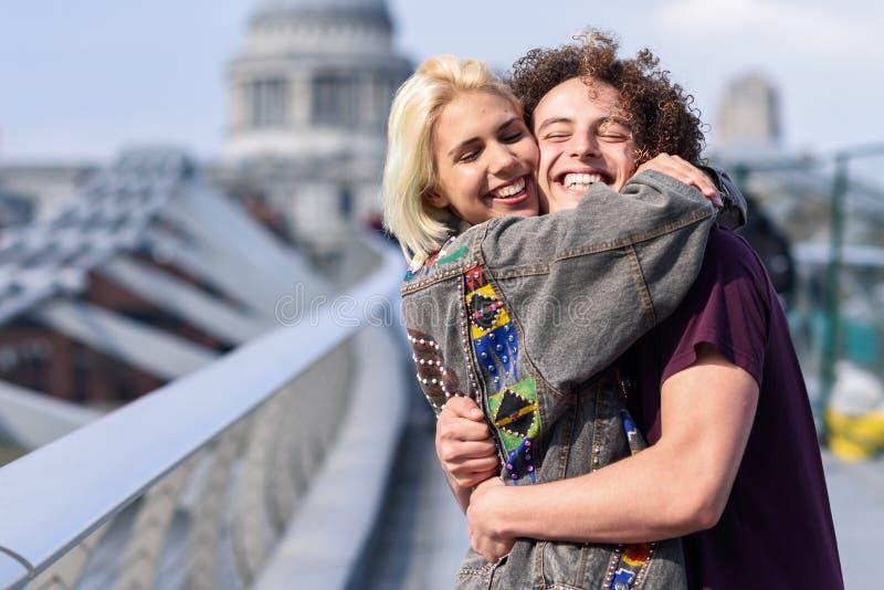 Gelukkig paar die door Millenniumbrug koesteren, Rivier Theems, Londen royalty-vrije stock foto