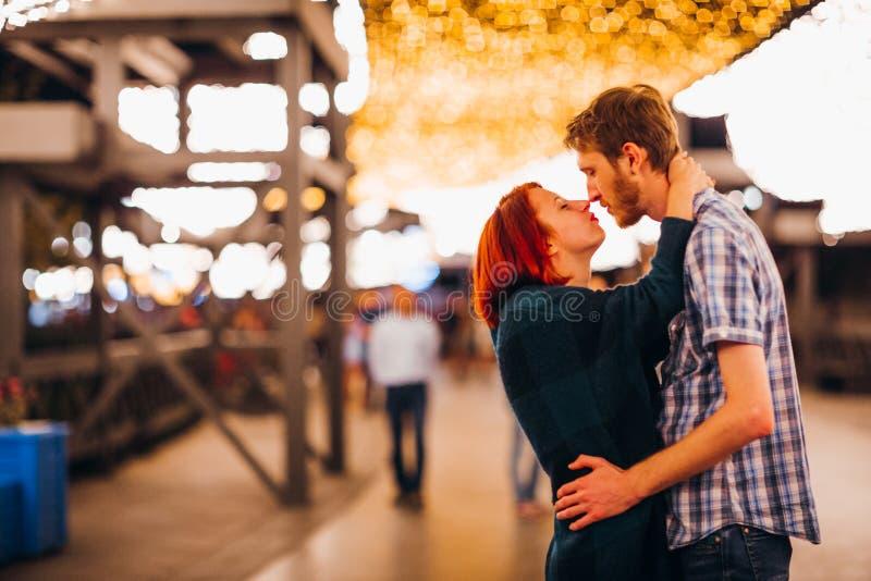 Gelukkig paar die en in de avond op lichte slingers omhelzen kussen royalty-vrije stock foto