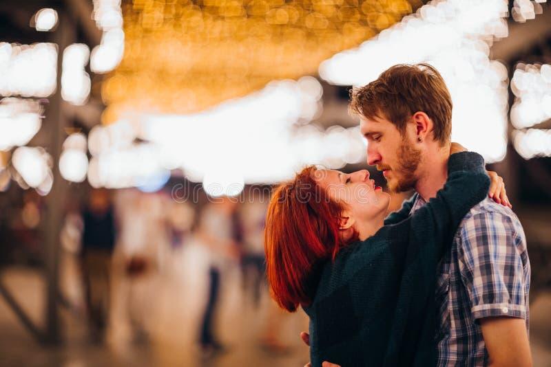 Gelukkig paar die en in de avond op lichte slingers omhelzen kussen stock afbeeldingen
