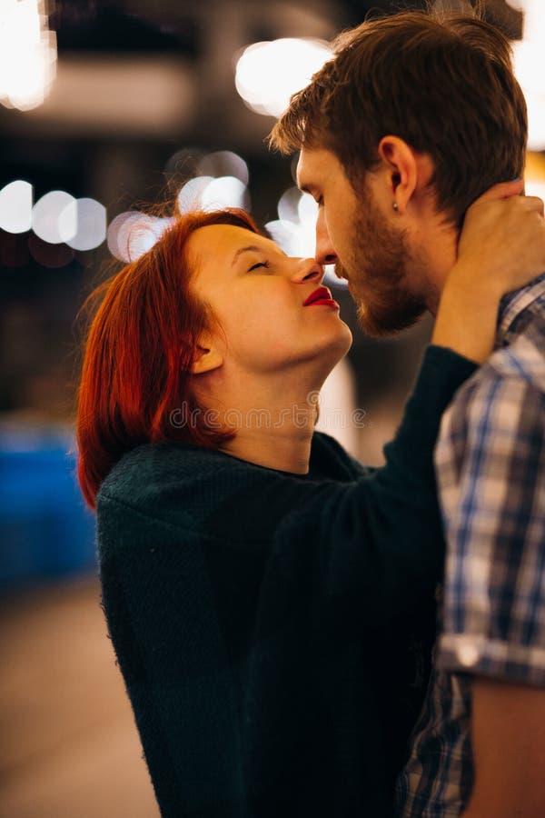 Gelukkig paar die en in de avond op lichte slingers omhelzen kussen stock afbeelding