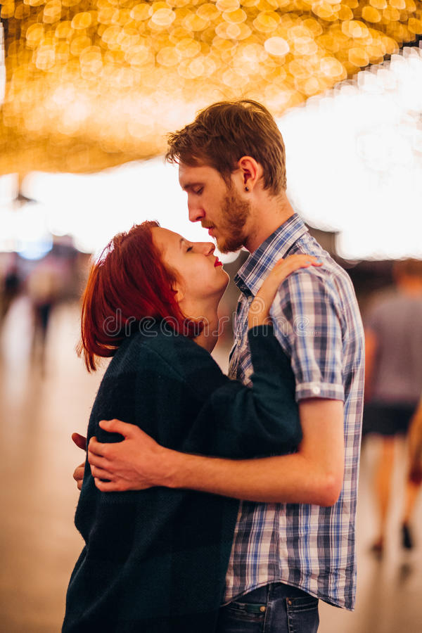 Gelukkig paar die en in de avond op lichte slingers omhelzen kussen royalty-vrije stock afbeeldingen