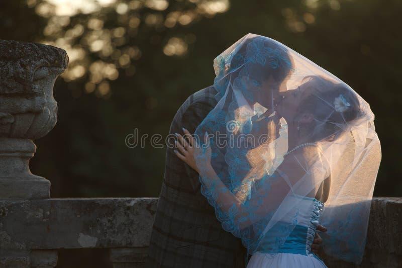 Gelukkig paar die en elkaar koesteren kussen onder sluier op backgr royalty-vrije stock fotografie