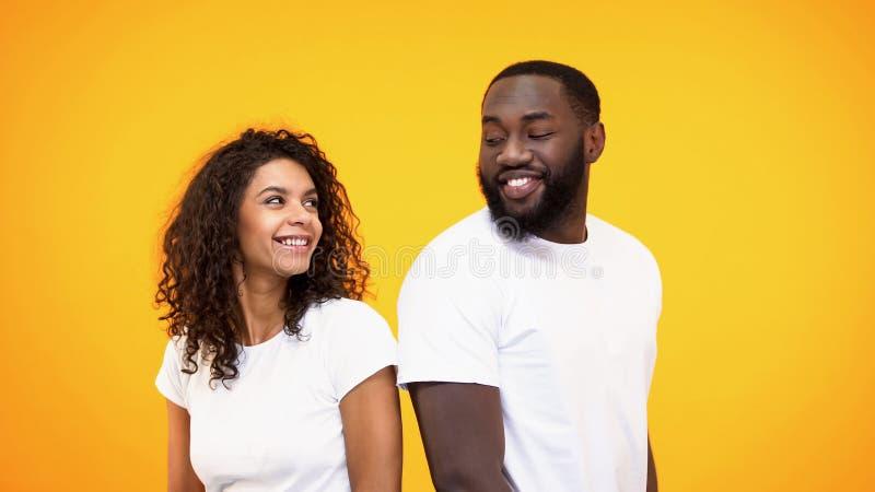 Gelukkig paar die en elkaar op gele achtergrond, kennis glimlachen flirten royalty-vrije stock foto