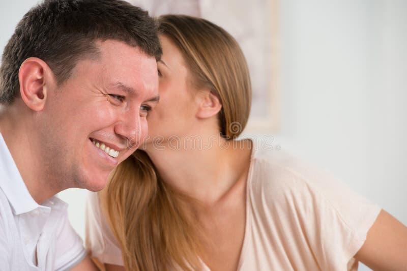 Gelukkig paar die en in hun woonkamer spreken roddelen stock fotografie
