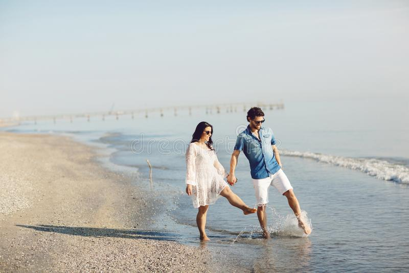 Gelukkig paar die en op het strand lopen spelen, die zijn voeten in het water doorweken Prachtig liefdeverhaal in Rimini, Italië stock foto