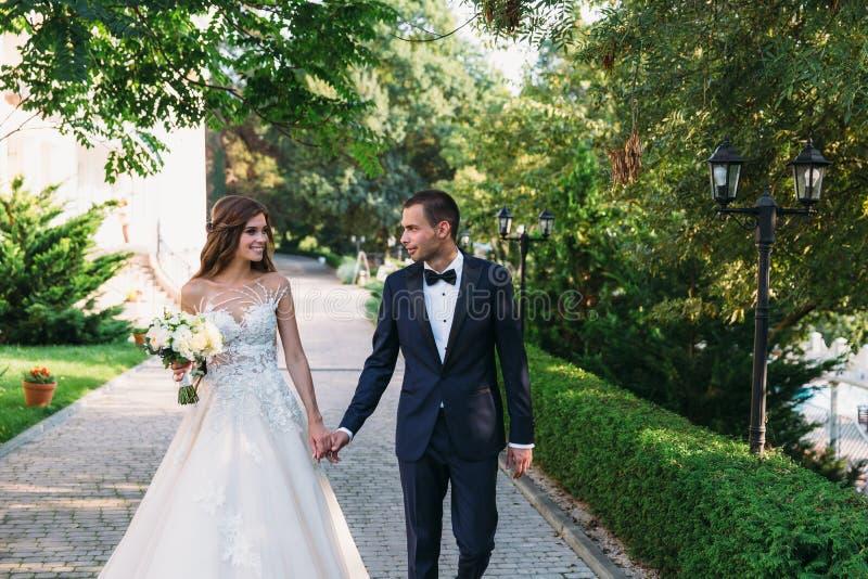 Gelukkig paar die en uit in het park koesteren hangen De bruid in een zwart kostuum met een vlinderdas en een bruid in mooi stock fotografie