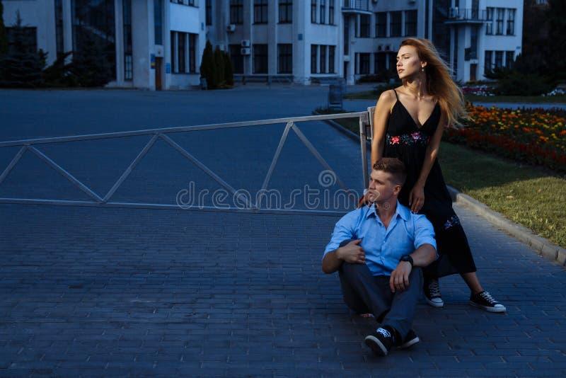 Gelukkig paar die en zich voor de stad omhelzen bevinden de donkere achtergrond, de zon glanst op minnaars royalty-vrije stock foto