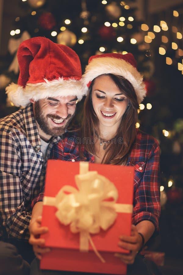Gelukkig paar die gift in doos Nieuwe jarenvooravond bekijken royalty-vrije stock afbeelding