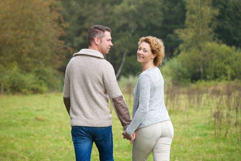Gelukkig paar die in het platteland lopen stock foto
