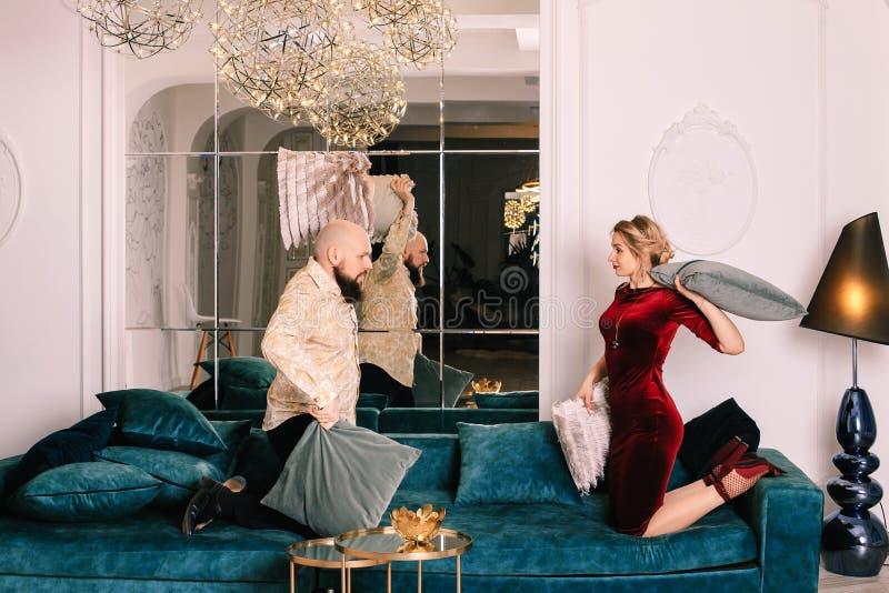 Gelukkig paar die hoofdkussenstrijd in bed hebben thuis royalty-vrije stock foto's