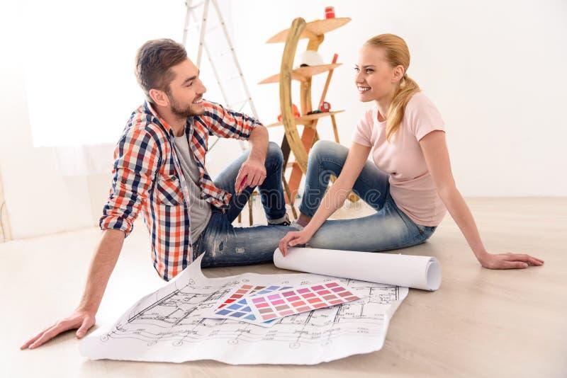 Gelukkig paar die hun nieuwe flat plannen royalty-vrije stock foto
