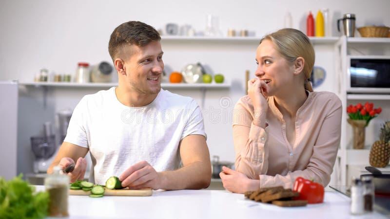 Gelukkig paar die, kokende salade van verse groenten, gezond gmo vrij voedsel flirten royalty-vrije stock fotografie