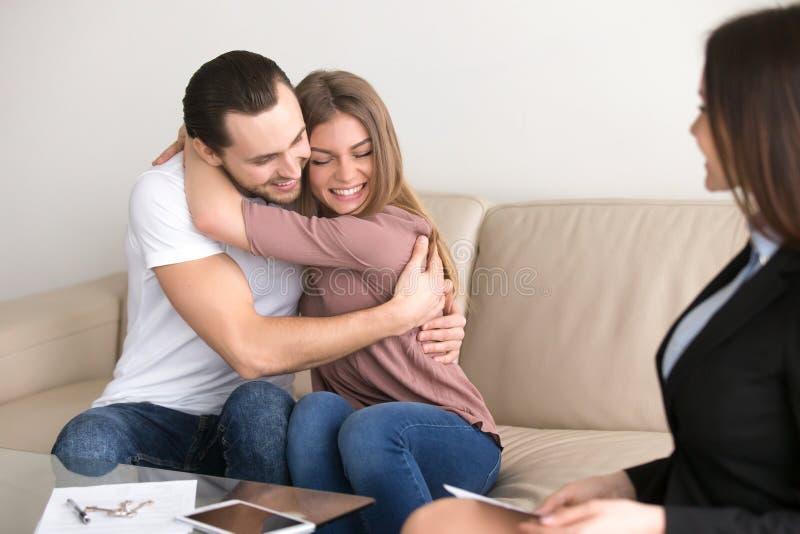 Gelukkig paar die kopende flatvergadering met onroerende goederen omhelzen stock foto's