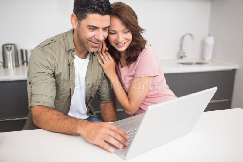 Gelukkig paar die laptop in keuken met behulp van royalty-vrije stock foto's