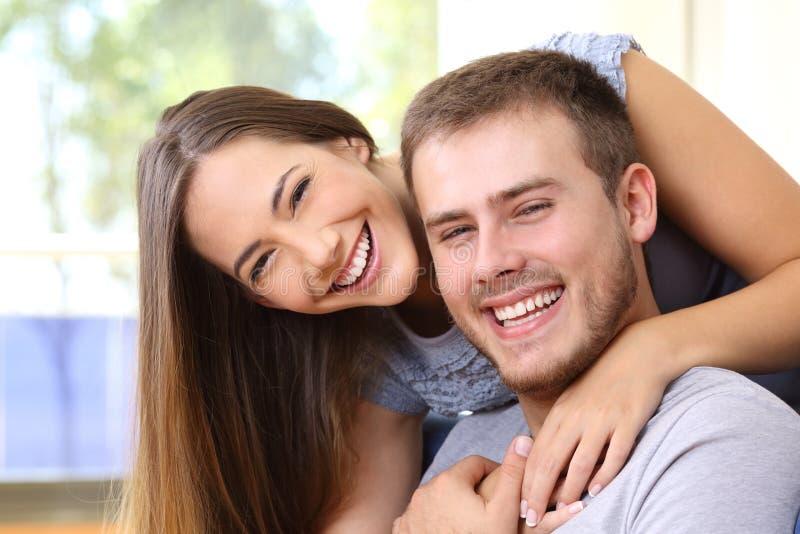 Gelukkig paar die met perfecte tanden thuis glimlachen stock foto's