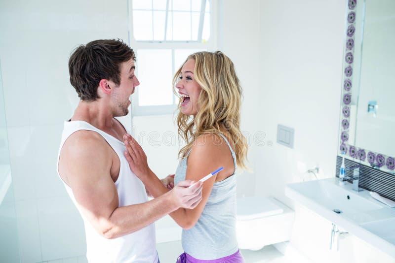 Gelukkig paar die met positieve zwangerschapstest worden opgewekt royalty-vrije stock foto's