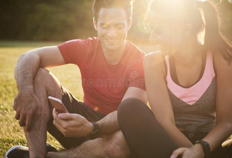 Gelukkig paar die mobiele telefoon in openlucht met behulp van stock foto's