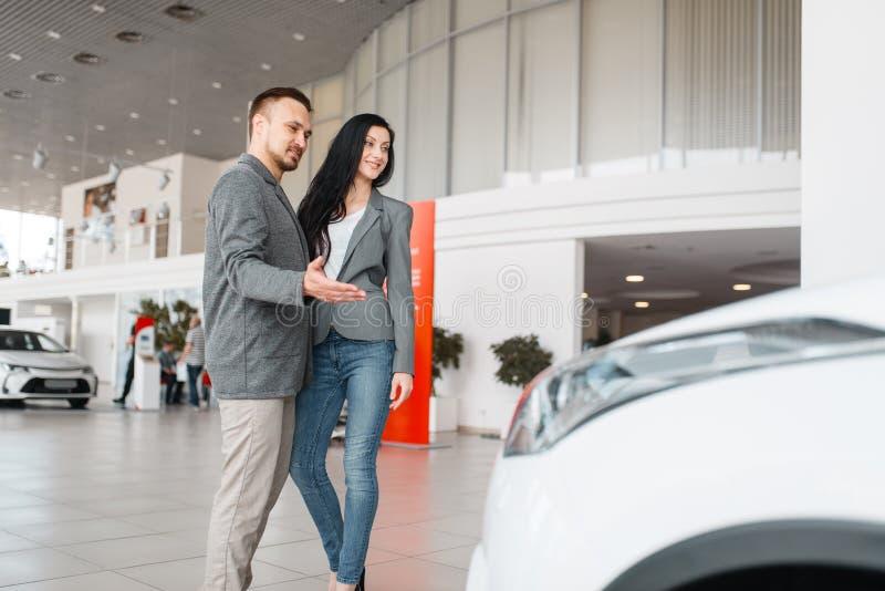 Gelukkig paar die nieuwe auto in toonzaal kopen stock fotografie