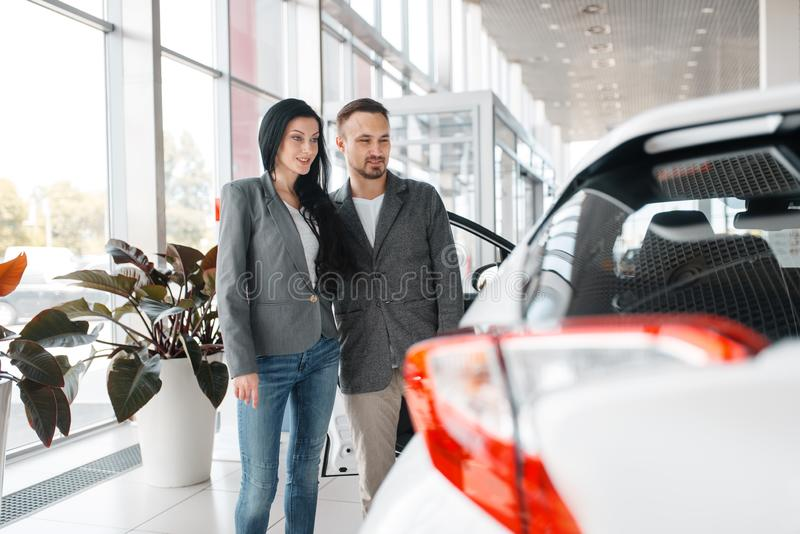 Gelukkig paar die nieuwe auto in toonzaal kopen stock foto's
