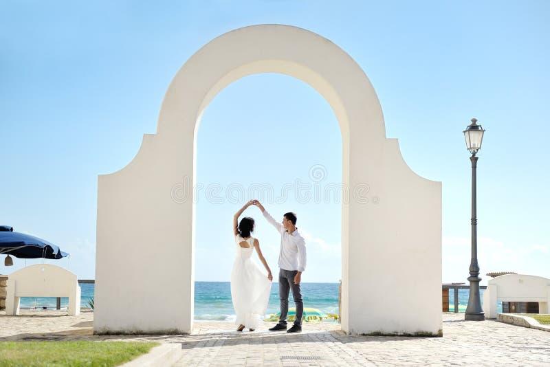 Gelukkig paar die onder een boog dichtbij overzees in Sperlonga, Italië dansen royalty-vrije stock foto's