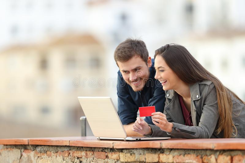 Gelukkig paar die online met creditcard en laptop betalen stock afbeelding
