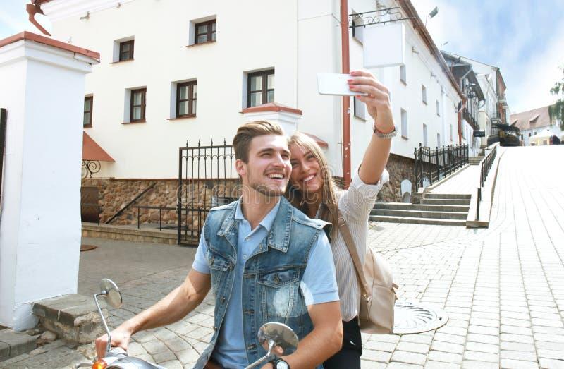 Gelukkig paar die op autoped selfie foto op smartphone in openlucht maken royalty-vrije stock afbeelding