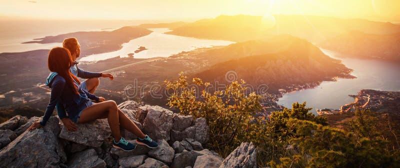 Gelukkig paar die op de zonsondergang in de bergen letten stock afbeelding