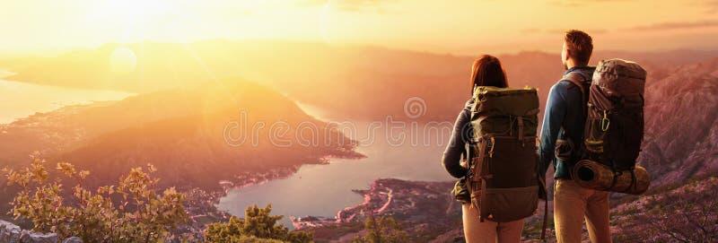 Gelukkig paar die op de zonsondergang in de bergen letten stock afbeeldingen