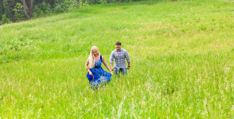 Gelukkig paar die op een weide in de zomeraard lopen stock foto