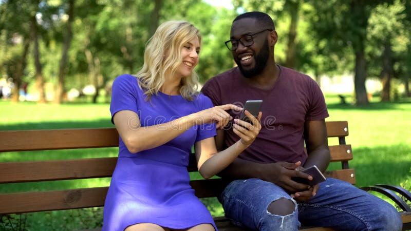Gelukkig paar die op grappige video's in netto op smartphone letten, die samen lachen stock foto's