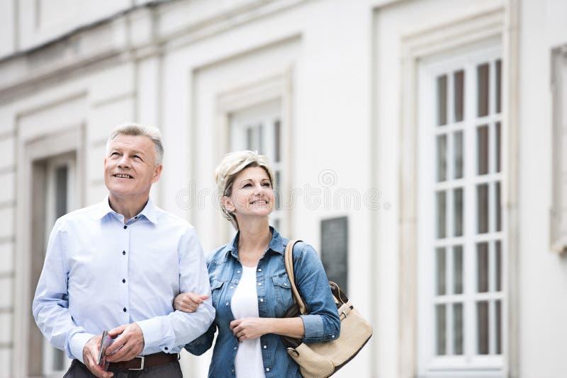 Gelukkig paar die op middelbare leeftijd zich met wapen in wapen buiten de bouw bevinden stock fotografie