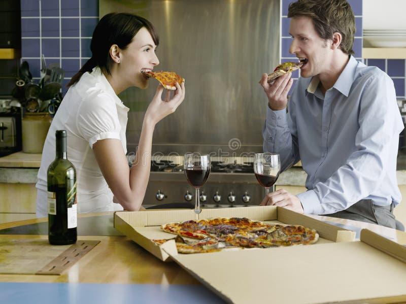 Gelukkig Paar die Pizza in Keuken eten royalty-vrije stock foto's