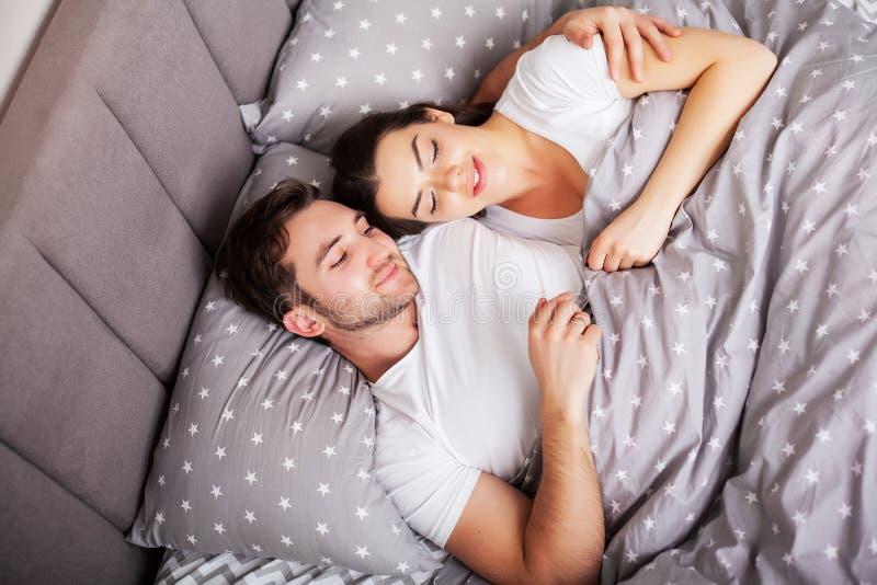 Gelukkig paar die pret in bed hebben Vertrouwelijk sensueel jong paar die in slaapkamer van elkaar genieten stock afbeeldingen