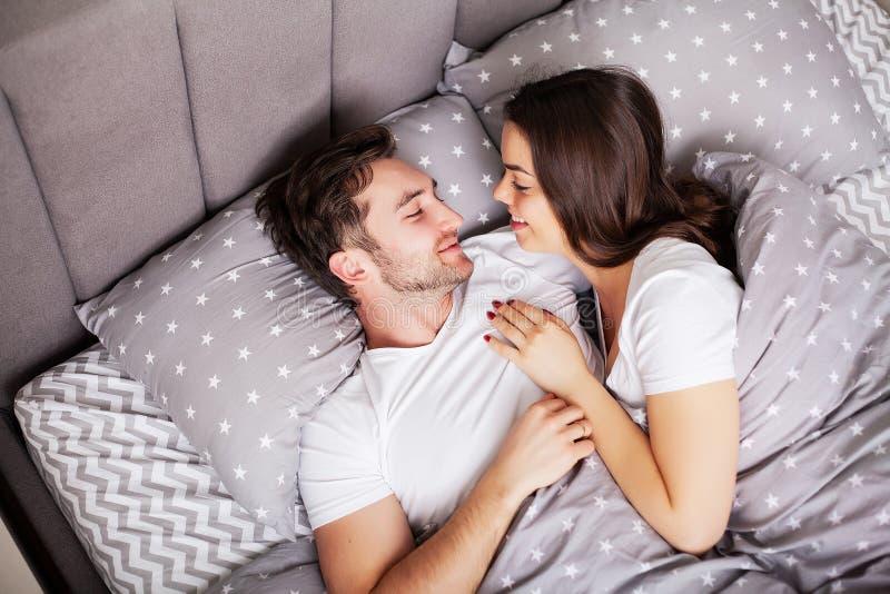 Gelukkig paar die pret in bed hebben Vertrouwelijk sensueel jong paar die in slaapkamer van elkaar genieten stock afbeelding