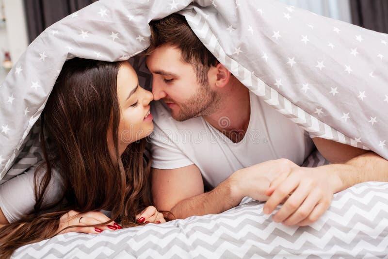 Gelukkig paar die pret in bed hebben Vertrouwelijk sensueel jong paar die in slaapkamer van elkaar genieten royalty-vrije stock afbeelding