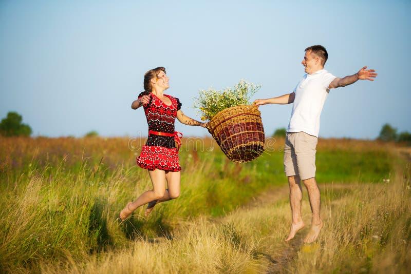 Gelukkig paar die pret in openlucht in de zomerweide hebben stock foto