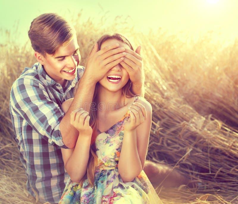 Gelukkig paar die pret in openlucht op tarwegebied hebben stock fotografie