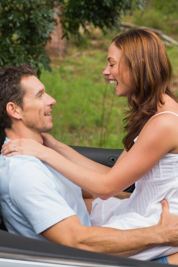 Gelukkig paar die romantisch in achterbank en het lachen voelen royalty-vrije stock fotografie