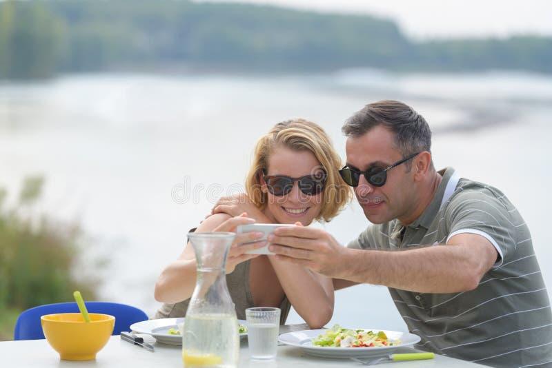 Gelukkig paar die selfie bij openluchtrestaurant nemen royalty-vrije stock afbeeldingen