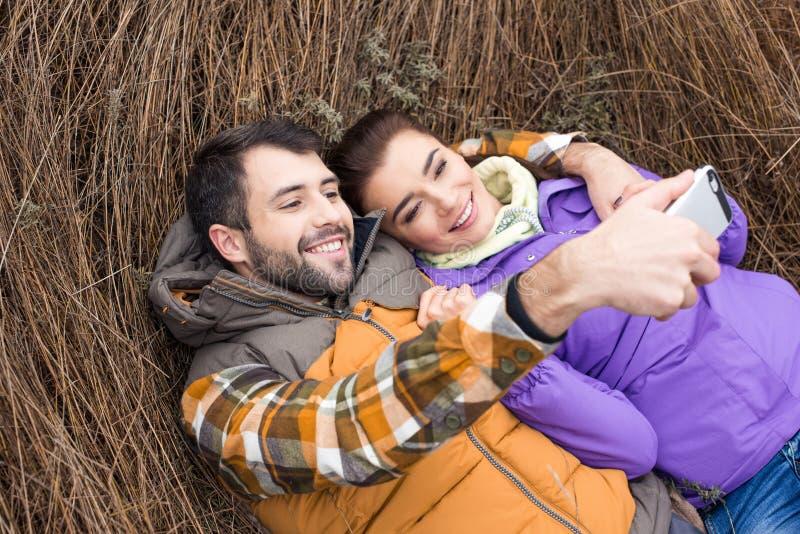 Gelukkig paar die selfie in gras nemen stock afbeeldingen