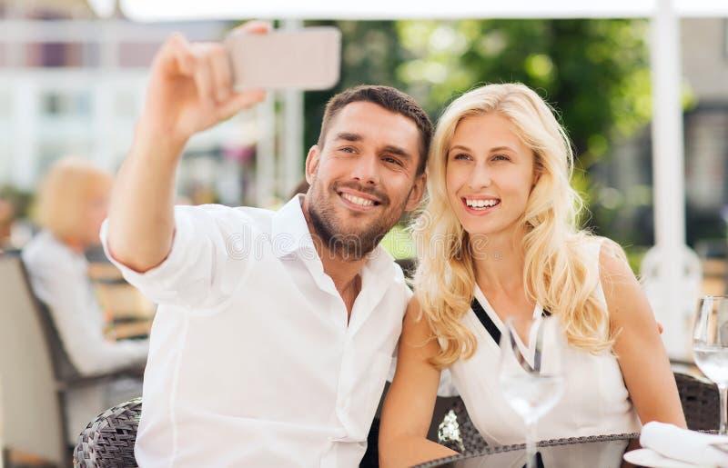 Gelukkig paar die selfie met smatphone bij koffie nemen stock foto