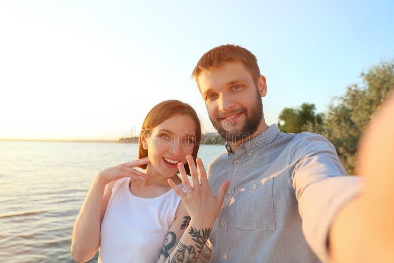 Gelukkig paar die selfie met verlovingsring dichtbij rivier op zonnige dag nemen stock afbeeldingen