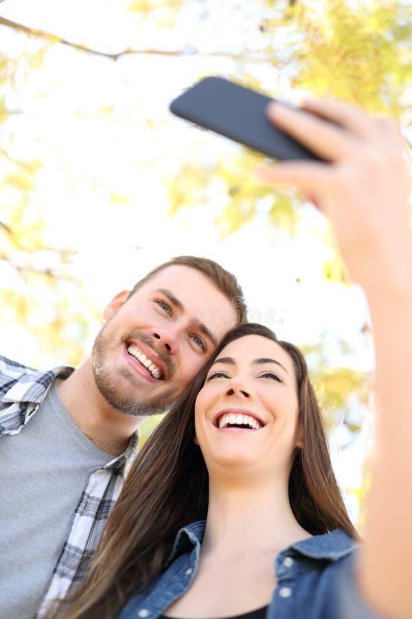Gelukkig paar die selfies met smartphone nemen stock afbeelding